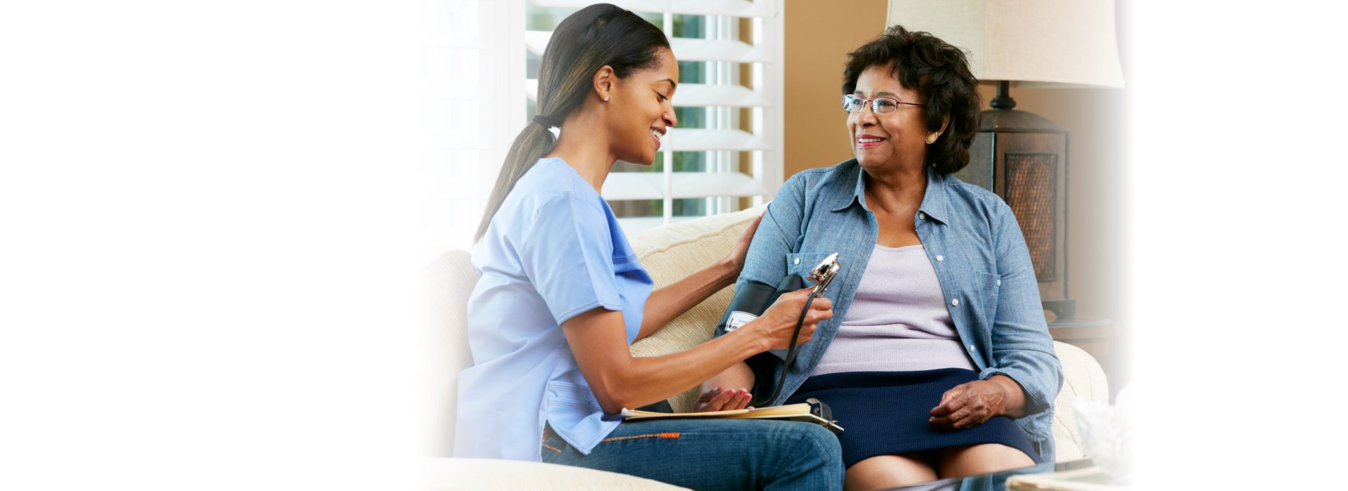 Nurse Visiting Senior Female Patient At Home Smiling
