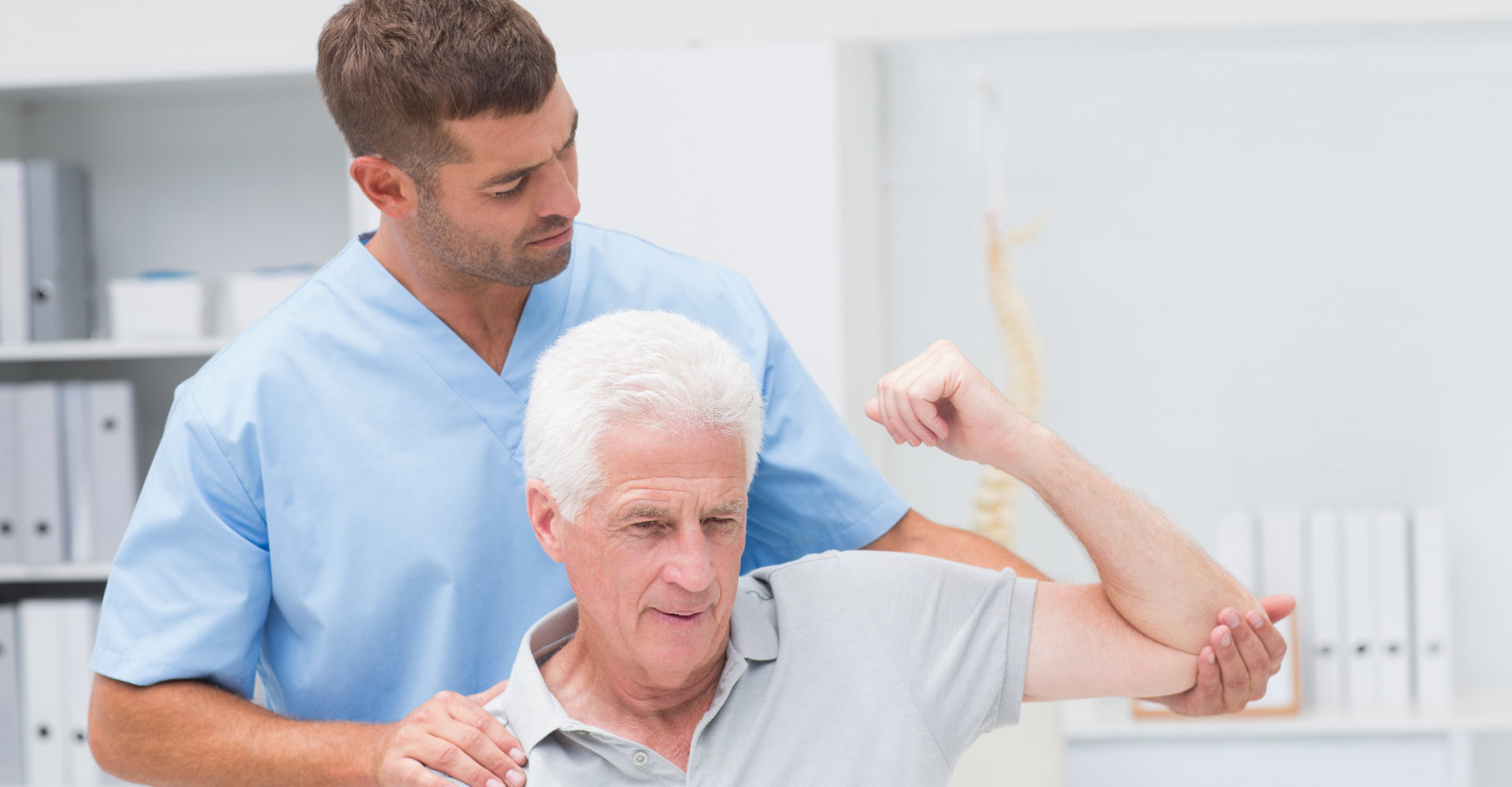 caregiver assisting patient in lifting his arm