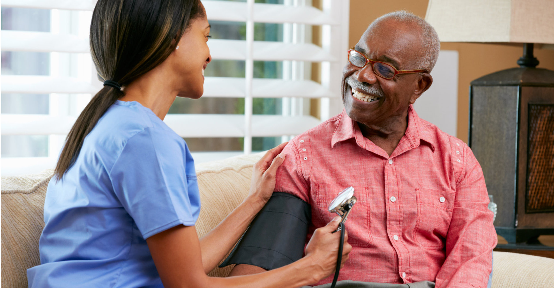 Nurse Visiting Senior Male Patient At Home Smiling