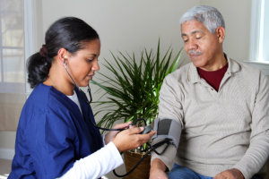 caregiver checking blood pressure of the old man